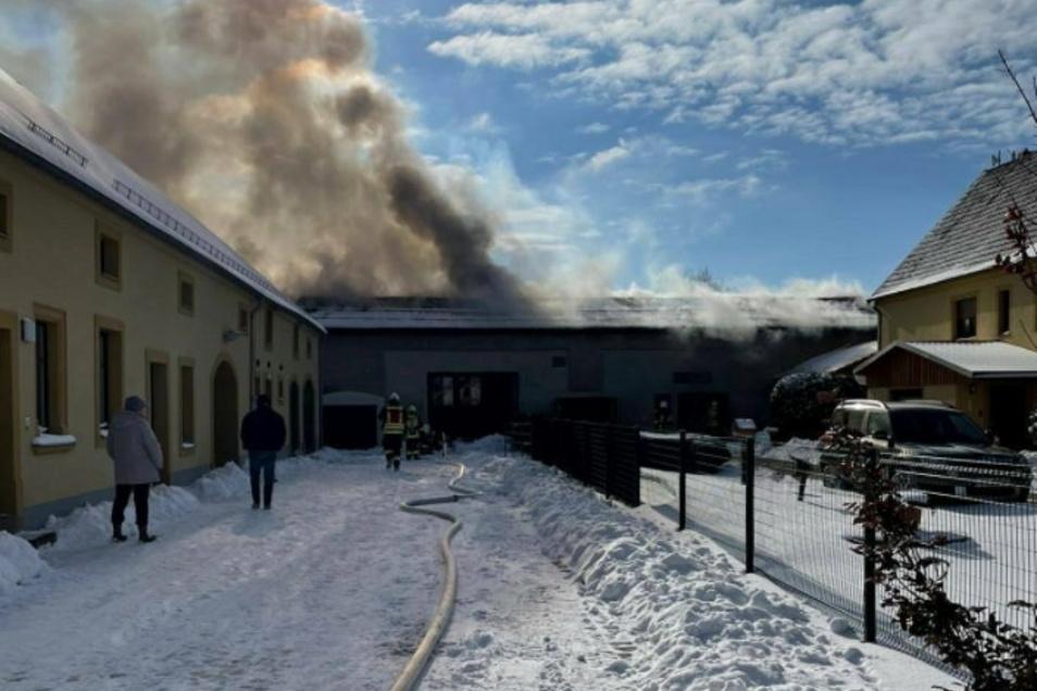 Aus einer ehemaligen Scheune in Lichtensee dringt Qualm. Die Feuerwehr hat Schläuche ausgerollt und mit dem Löschen begonnen.