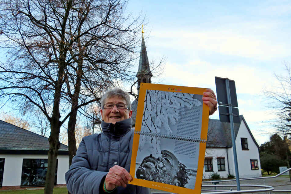 """Irene Hoffmann freut sich über den """"Anderen Adventskalender"""", der ihr an jedem neuen Tag Mut, Hoffnung und Freude bringt. Im Hintergrund zu sehen: das Hoyerswerdaer Martin-Luther-King-Haus, in dem sie lange Zeit ehrenamtlich gewirkt hat."""