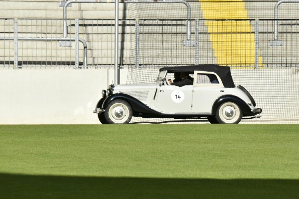 Ein Mercedes V170von 1951 umrundet den Rasen, auf dem sonst die Fußballer von Dynamo Dresden spielen.