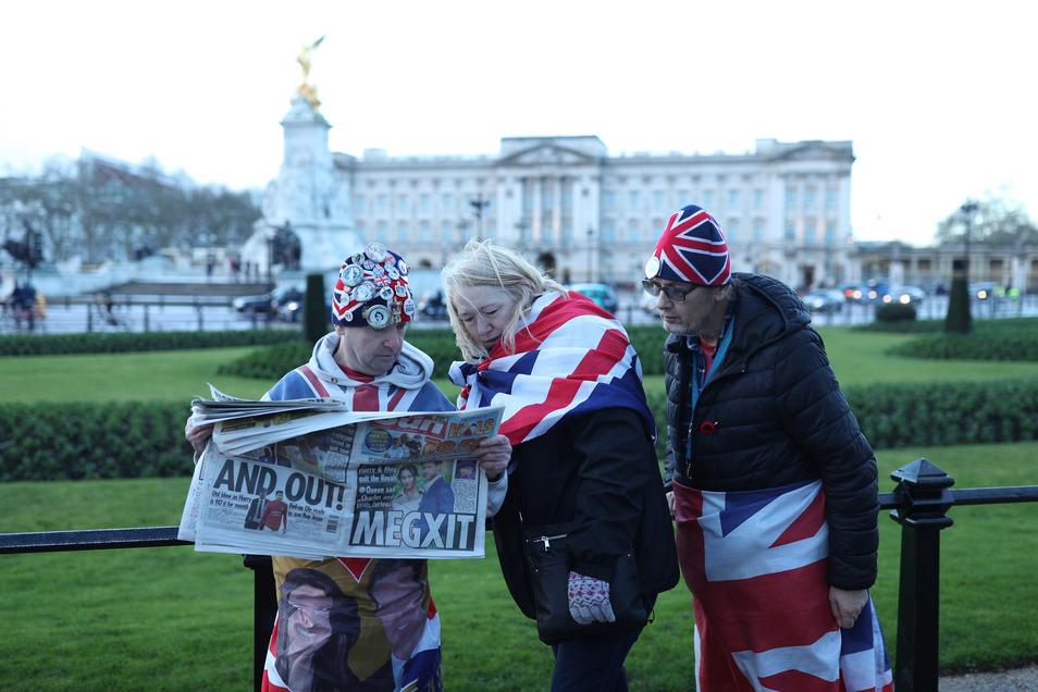 """Fans lesen die Tagezeitung """"The Sun"""" vor dem Buckingham Palace, nachdem bekannt wurde, dass Prinz Harry und Herzogin Meghan teilweise von ihren royalen Verpflichtungen zurücktreten."""