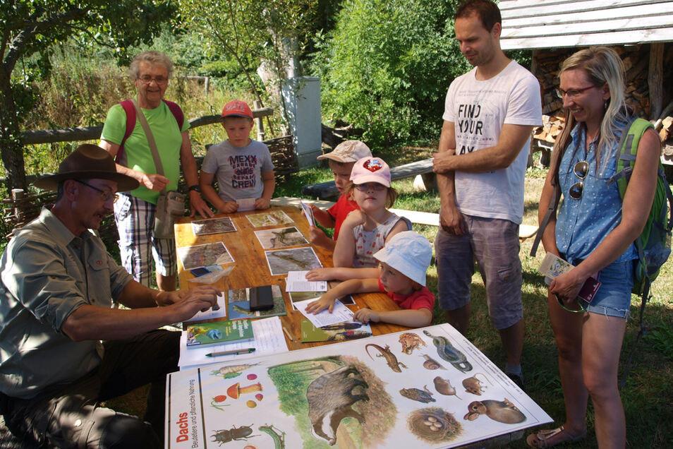 Die Kinder der Familie Trepte aus Schirgiswalde ließen sich hier vom Ranger Maik Rogel (li) die Lebensweise der heimischen Eidechsen erklären.