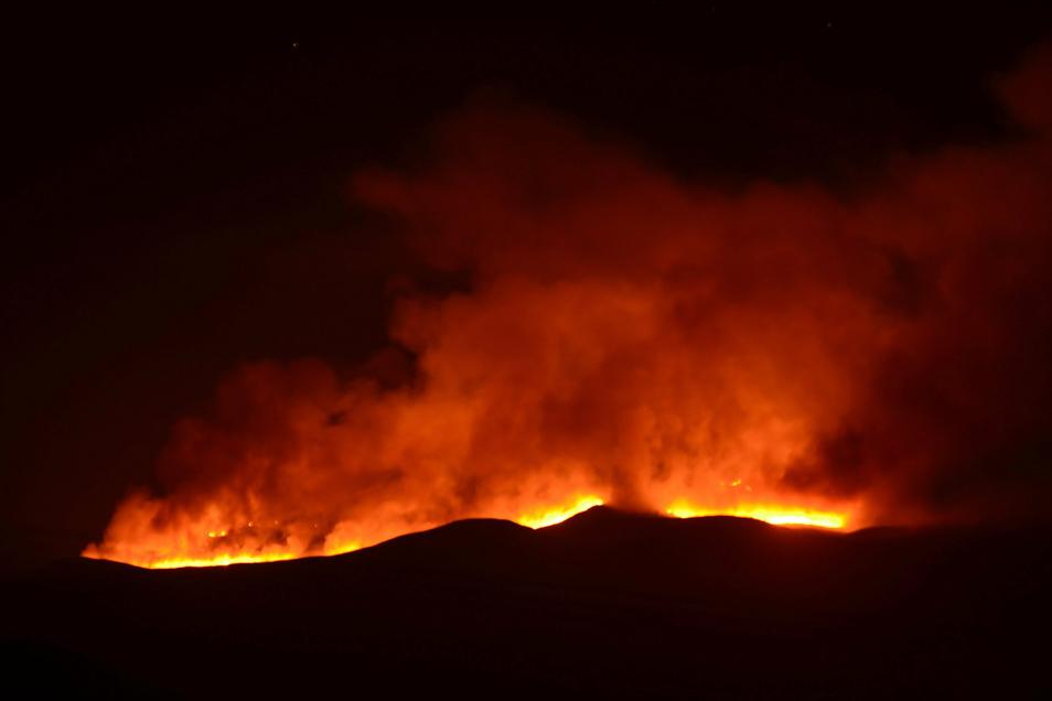 Hell scheinen die Flammen eines Feuers auf dem Kilimandscharo.