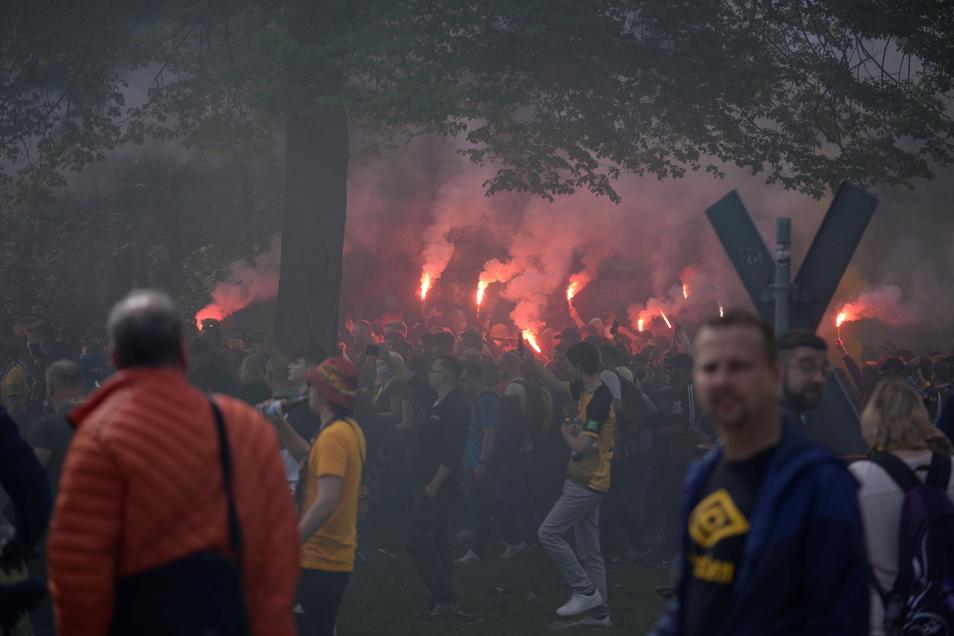 Mit brennenden Fackeln zieht ein grölender Pulk durch den Großen Garten in Richtung Stadion.
