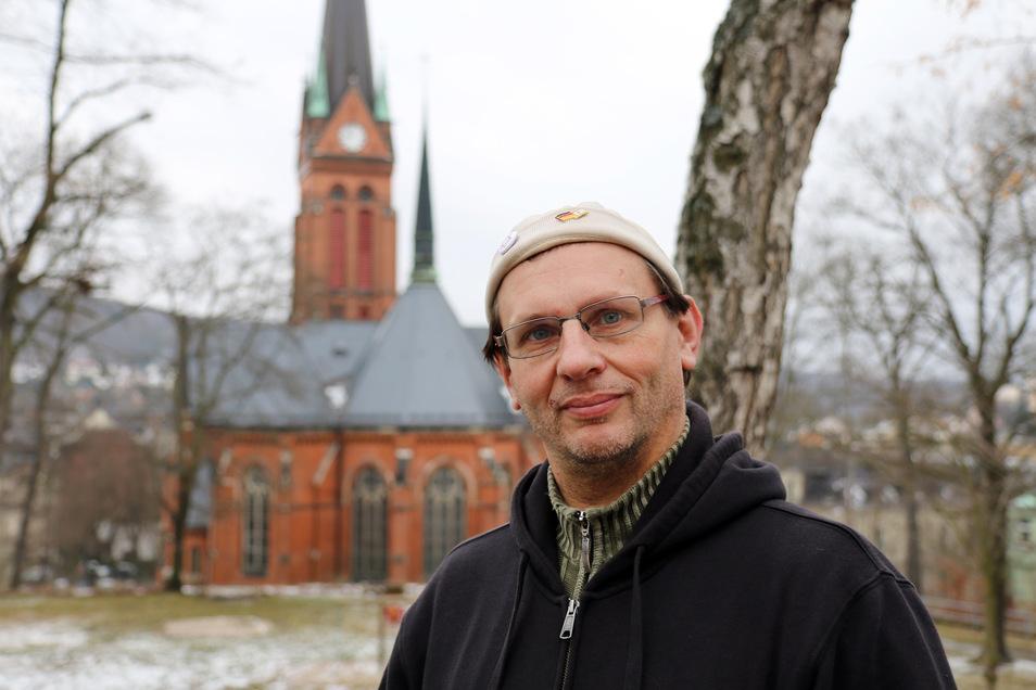 Mike Weller steht in einem Park vor der Nicolaikirche in Aue. Im Pfarrhaus der Kirchgemeinde war der Gemeindehelfer bei einer Weihnachtsfeier zu Heiligabend schwer verletzt worden.