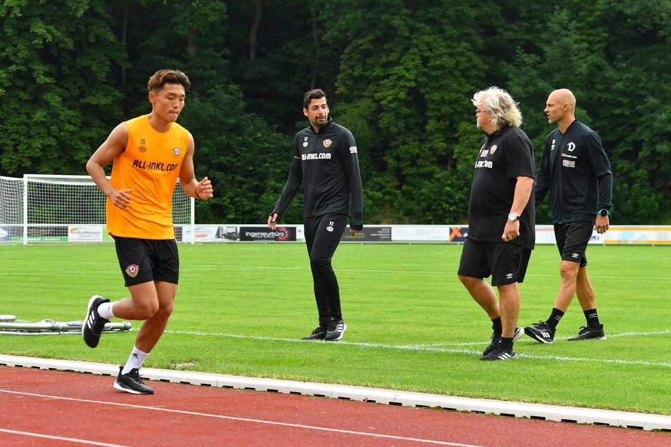 Die Co-Trainer Ferydoon Zandi und Heiko Scholz sowie Trainer Alexander Schmidt schauen Jong-min Seo beim Laktattest zu. Dieser sieht sehr konzentriert aus.
