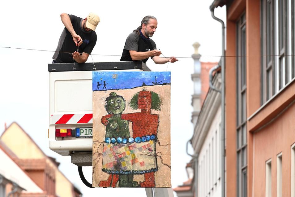 """Udo Hartmann (rechts) und Johannes Mitteldorf von den Stadtwerken Pirna hängen in der Schmiedestraße das Gemälde """"Nah und etwas ferner"""" von Bernd Fenk auf. Es gehört zur Straßengalerie mit insgesamt 26 Bildern."""