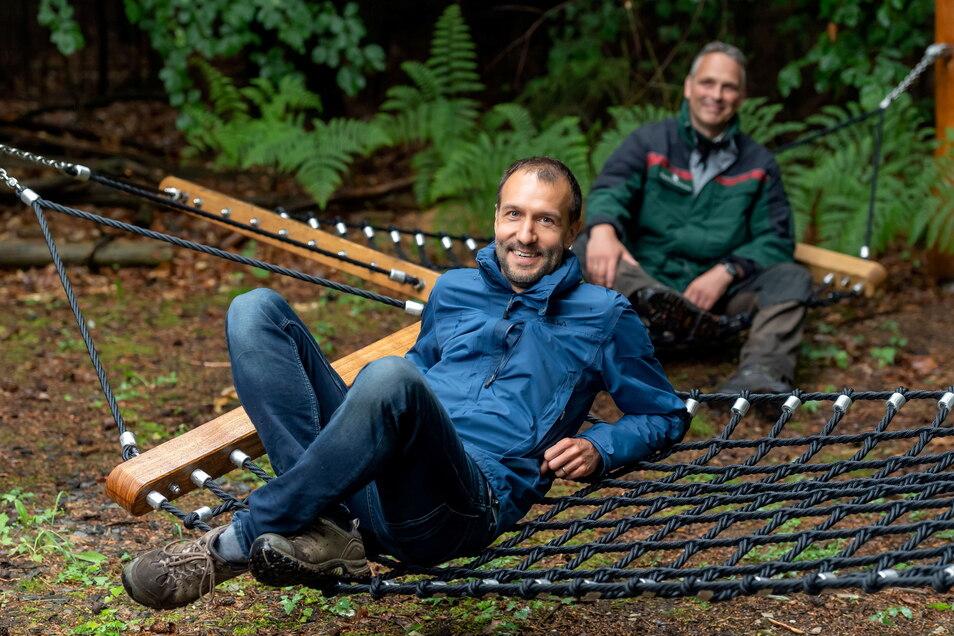 Reinhardtsdorf-Schönas Bürgermeister Andreas Heine (vorn) und Forstbezirksleiter Uwe Borrmeister testen schon mal die Waldhängematten.