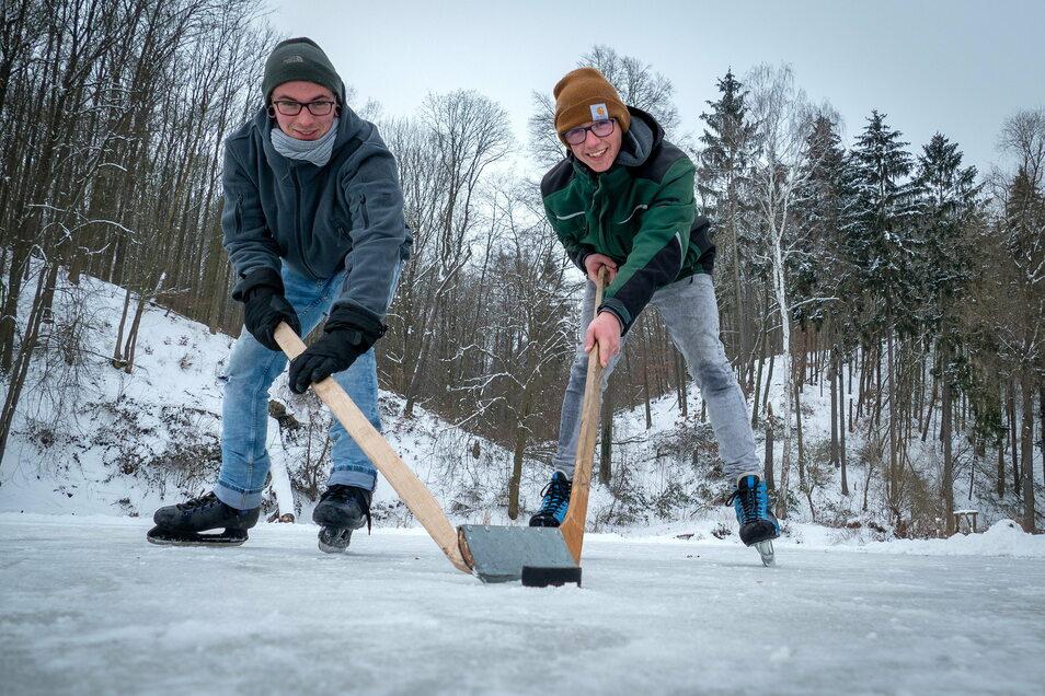 Dominik (links) und Frederik aus Wendishain spielen auf dem Angelteich an der Muldenwiese in Westewitz Eishockey.