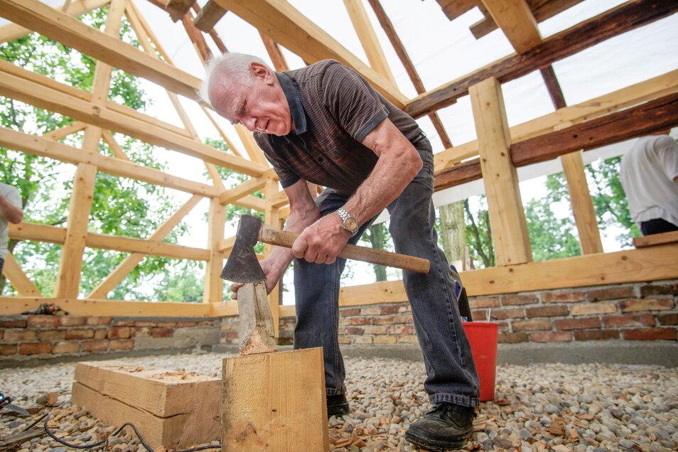 Harry Gottschlin bearbeitet die Staken mit einer Axt, bevor sie in die Gefache des Scharfrichterhauses eingepasst werden, wo sie als Basis für den Wurflehm dienen.