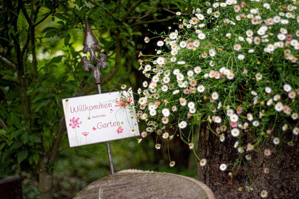Mit einem besonderen Schild werden Gäste im Garten begrüßt.