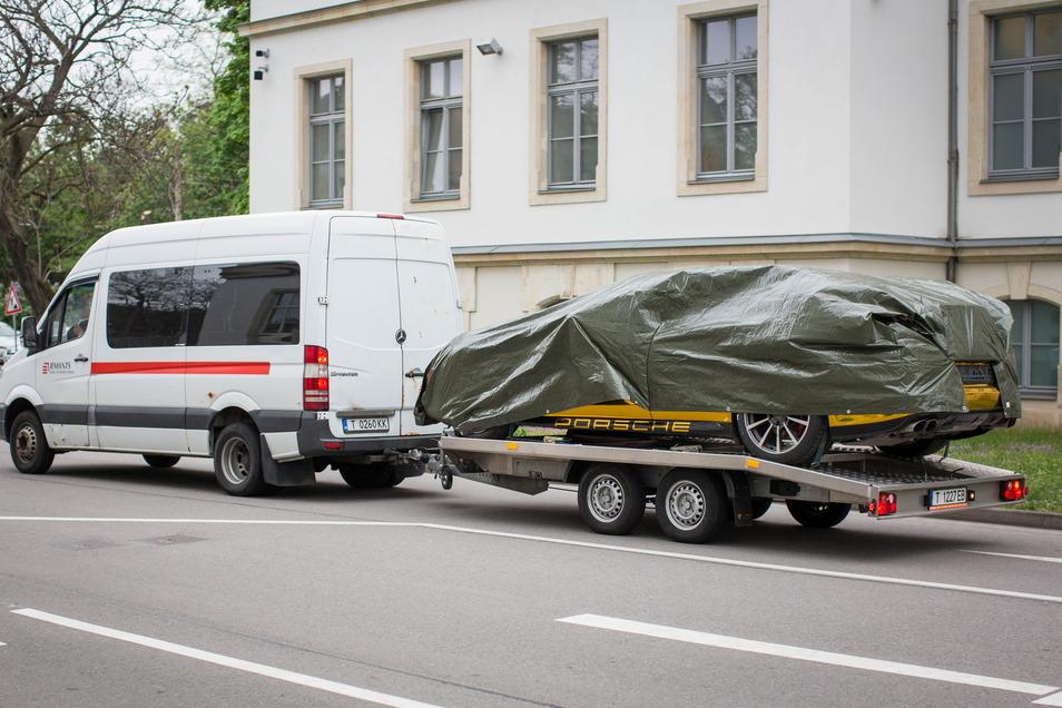 Der goldene Porsche darf wegen seiner spiegelnden Folierung, die in Deutschland verboten ist, nur abgedeckt transportiert werden.