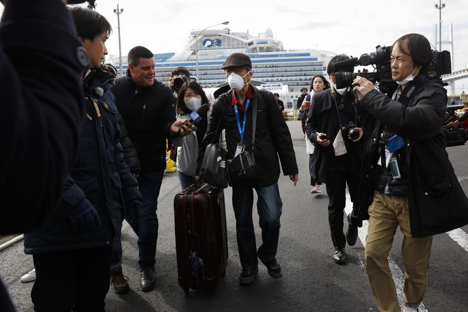 Ein Passagier wird von Journalisten empfangen, nachdem er das Kreuzfahrtschiff verlassen hat.