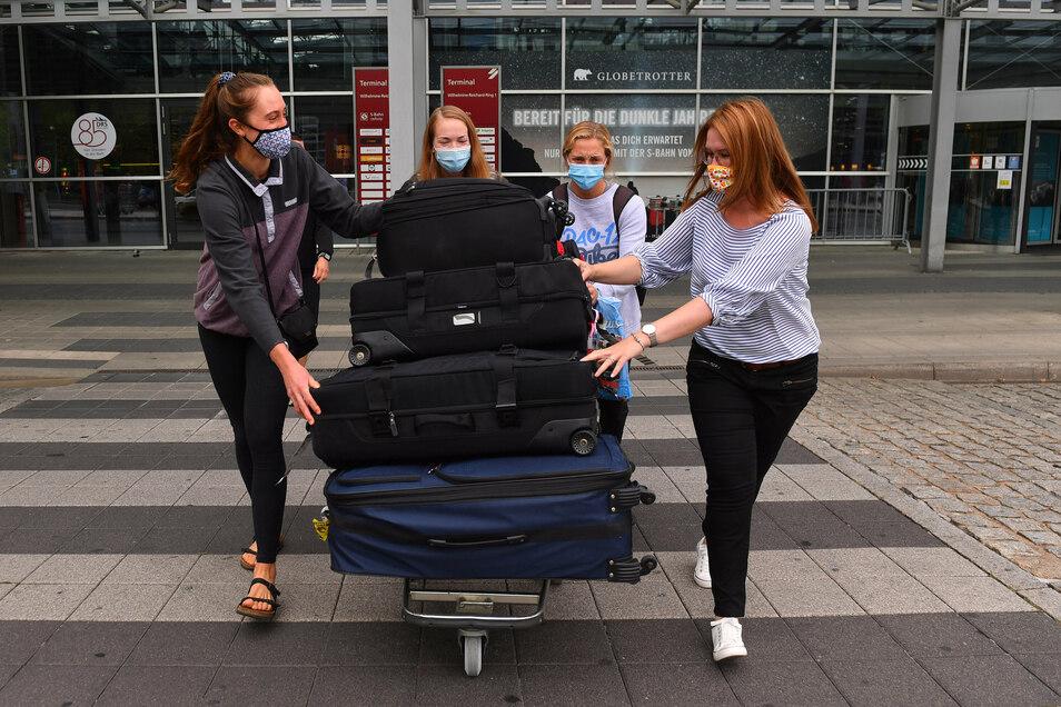 Madeleine Gates, Jenna Gray, Morgan Hentz und Geschäftsführerin Sandra Zimmermann (v.l.) rollen die Koffer zum Auto, natürlich vorbildlich mit Maske.