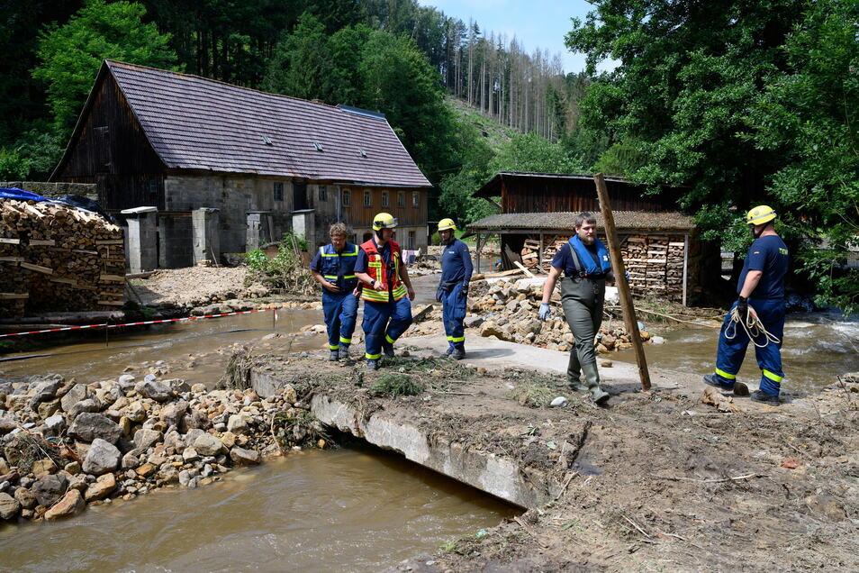 Einsatzkräfte des THW beseitigen Mitte Juli am Krippenbach in Krippen Geröll und begutachten die Schäden.