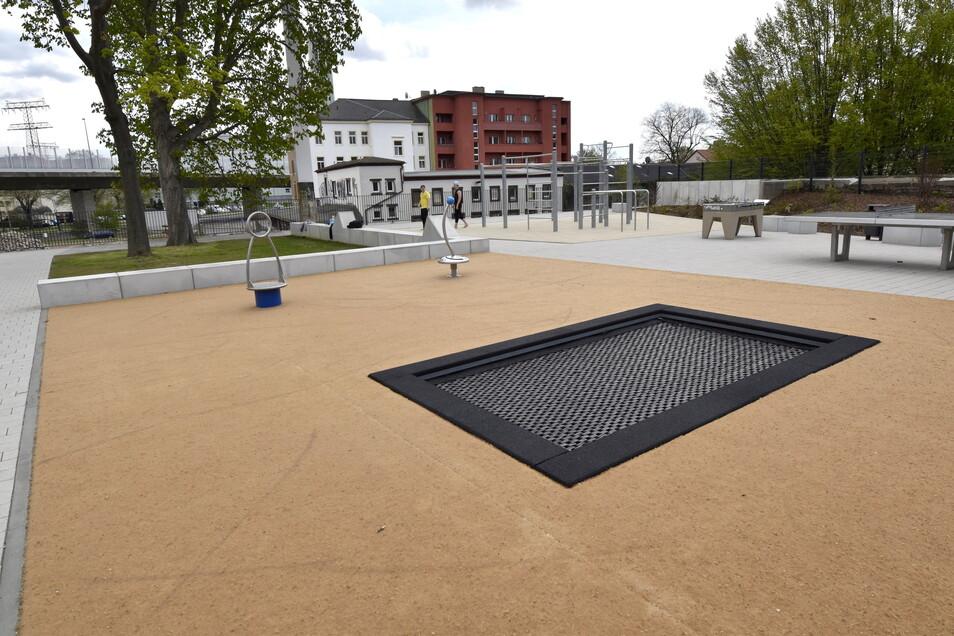 Das Trampolin ist in den Boden eingelassen, daneben stehen eine Tischtennisplatte und ein Tisch-Kicker, in Richtung Weißeritz schließt sich die Calisthenics-Anlage an.