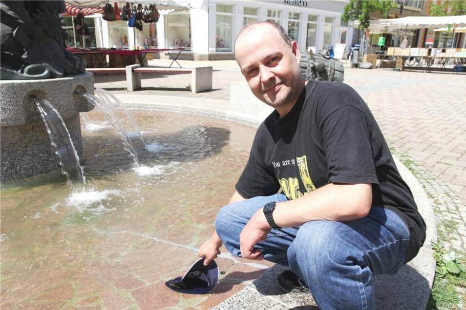 Der Döbelner René Schmidt taucht seine Mütze ins Brunnenwasser.