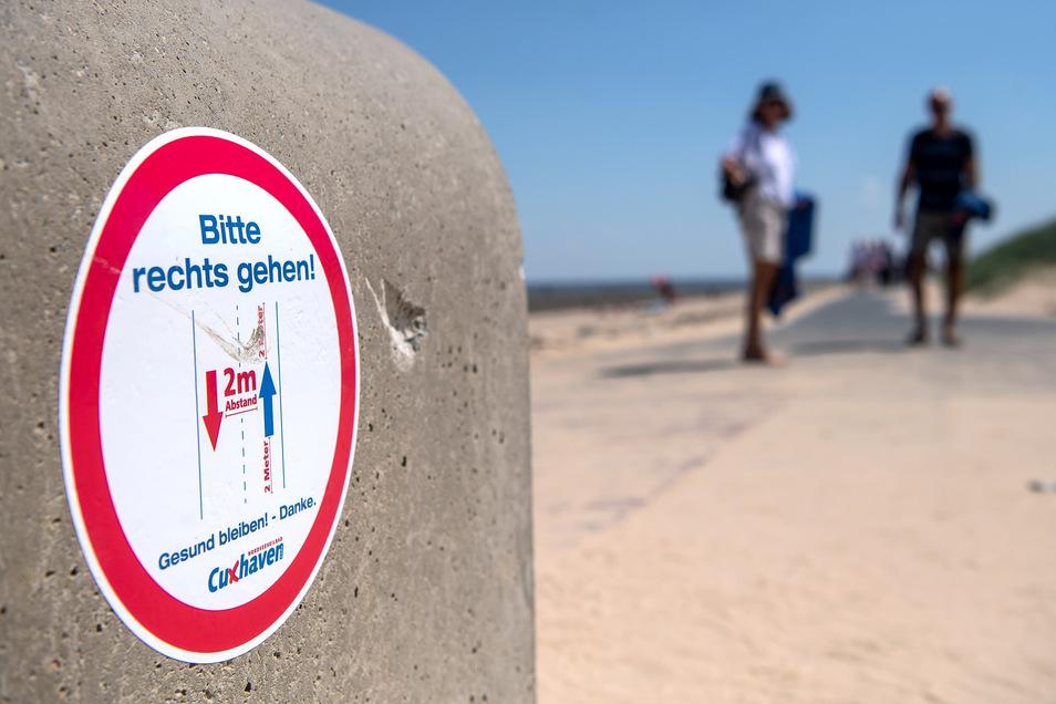 Niedersachsen, Cuxhaven: Ein Schild am Strand weist auf die vorgeschriebenen Laufrichtungen und Sicherheitsabstände hin.