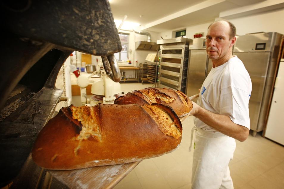 Lutz Chichowitz ist einer von drei Bäckern der Klosterbäckerei, die von der Behindertenwerkstatt St. Michael betrieben wird. Hier holt er gerade heißes Brot aus dem fast 95 Jahre alten Backofen der Marke Schmidt & Söhne. Er sorgt für die unverwechselbare