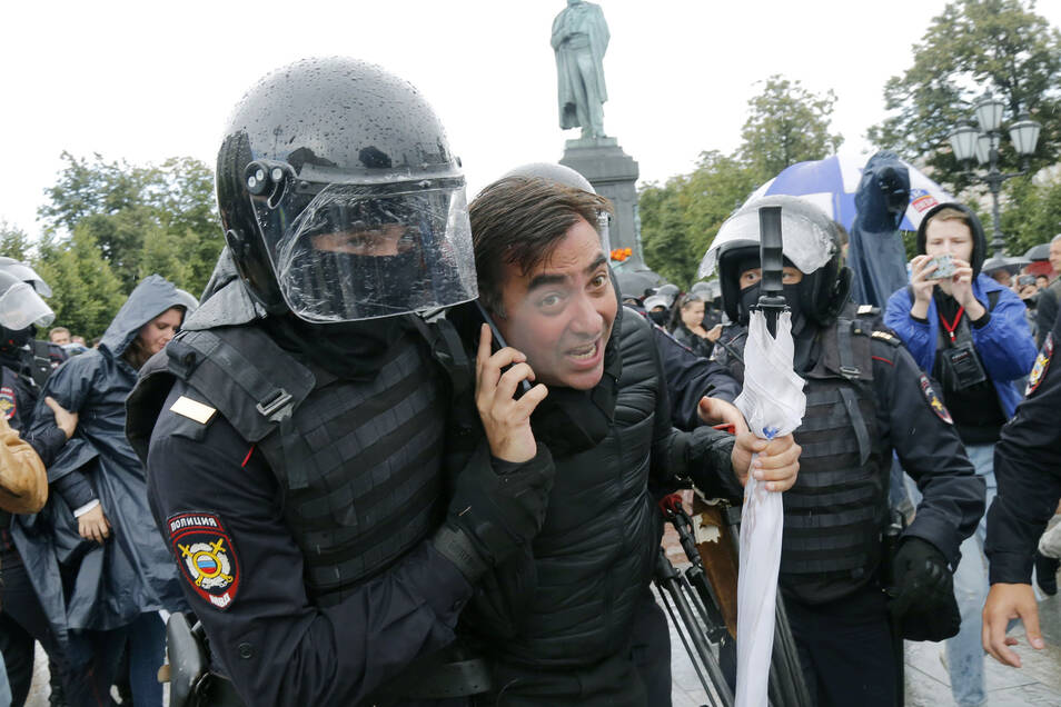 Ein Polizist führt am 3. August in Moskau einen Teilnehmer der nicht genehmigten Kundgebung im Stadtzentrum ab.