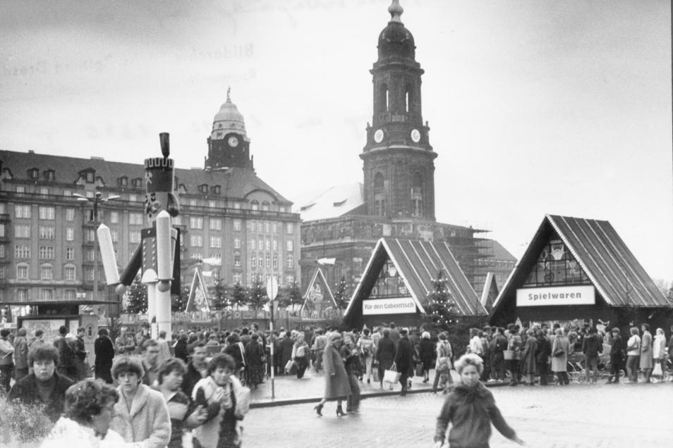 """1984: Hütten mit """"Spielwaren"""" und Dingen """"Für den Gabentisch"""" stehen auf dem Striezelmarkt auf dem Altmarkt. Davor ein Riesennussknacker."""