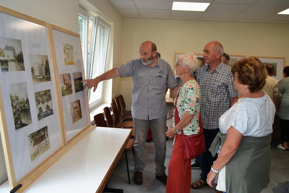 """Der Linzer Ortschronist Frank Schneider (l.) führt Besucher durch die Ausstellung """"Linzer Maler und ihre Bilder""""."""