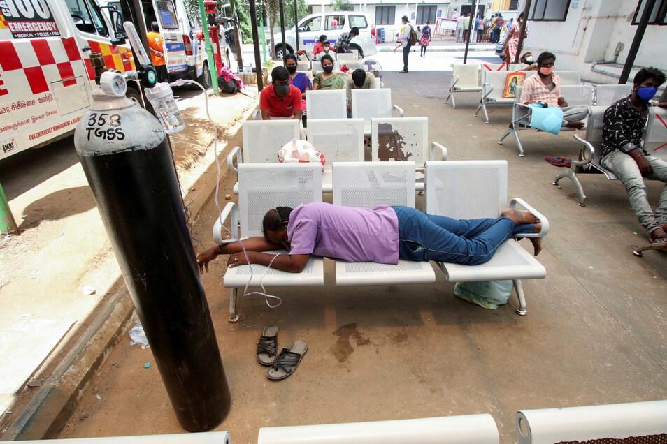 Ein an Covid-19 erkrankter Mann liegt in Indiens auf einer Bank und wird mit Sauerstoff versorgt, während er auf seine Aufnahme ins Krankenhaus wartet.