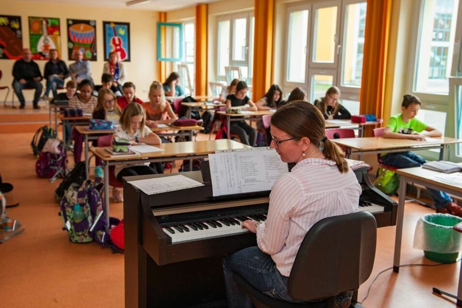 """Musiklehrerin Claudia Zobelt (vorn) studiert gerade mit den Schülern der Klasse 7a das Lied """"Kaputt"""" der Band """"Wir sind Helden"""" ein, als die Tür aufgeht und die polnischen Kollegen sich selbst ein Bild von der Arbeit an einer deutschen machen möchten."""