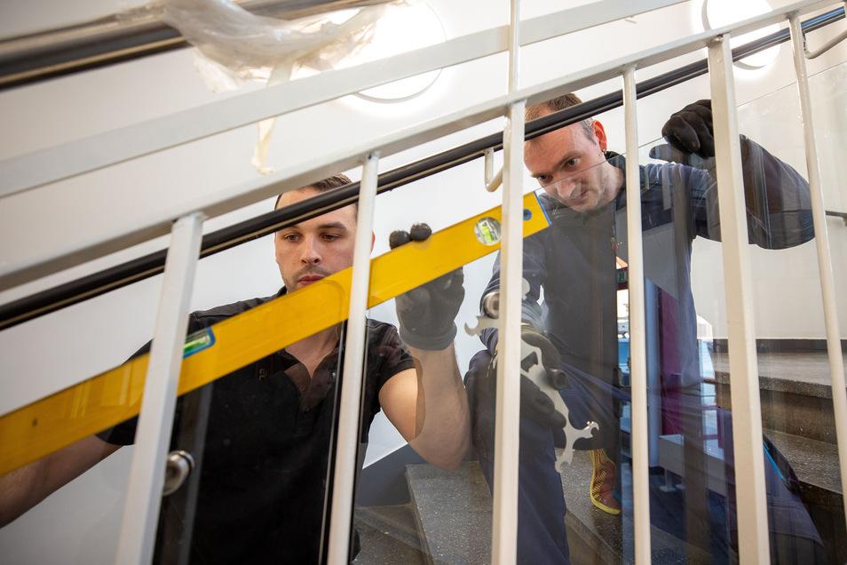 Unfallschutz für Fortgeschrittene: Vor den Geländerstreben montieren Arbeiter Schutzglas, damit niemand mehr durchpasst.