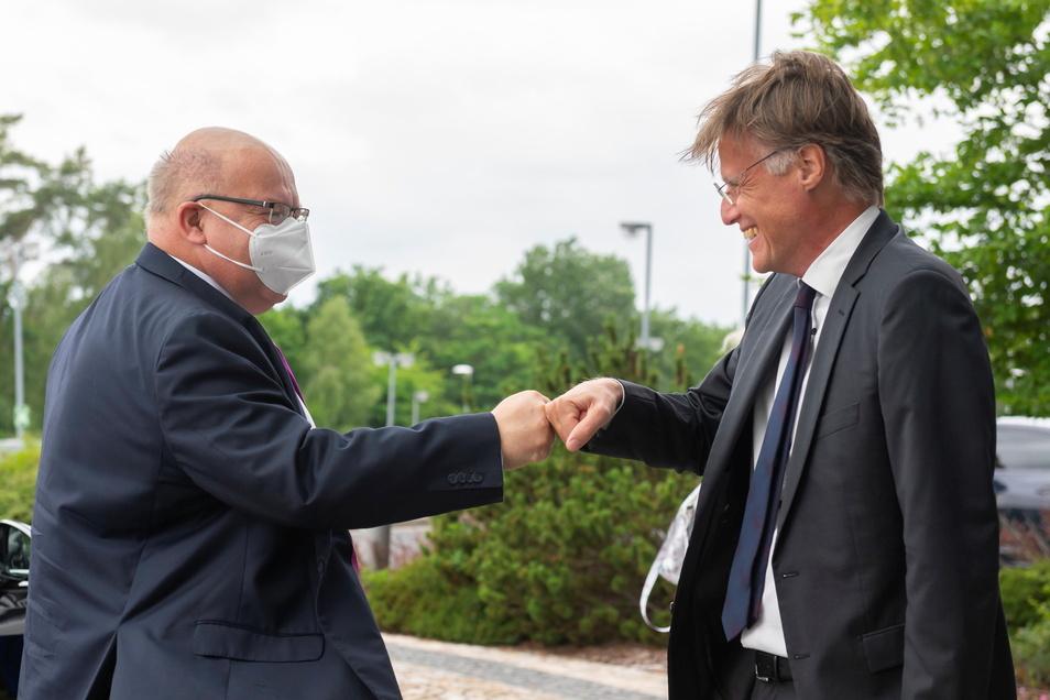 Coronagerechte, aber freundliche Begrüßung: Infineon-Vorstand Jochen Hanebeck (rechts) Faust an Faust mit Bundeswirtschaftsminister Peter Altmaier (CDU) vor der Infineon-Fabrik in Dresden.