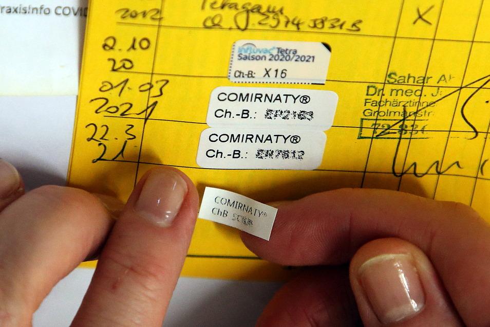 Eine Ärztin klebt den Nachweis für die dritte Impfung mit dem Comirnaty-Impfstoff des Herstellers Biontech/Pfizer in ein Impfbuch. Für Personen über 70 Jahre sind die Booster-Impfungen jetzt möglich. Die Inzidenz im Landkreis Meißen liegt bei 47,0.