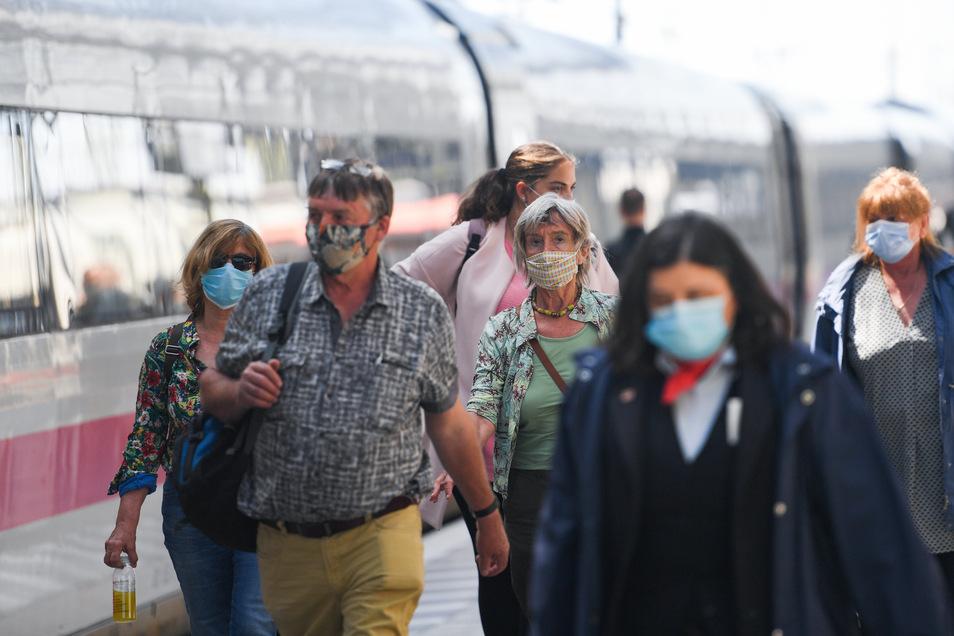 Nach der Ankunft eines ICE im Frankfurter Hauptbahnhof gehen die Reisenden mit Mundschutz am Zug entlang.