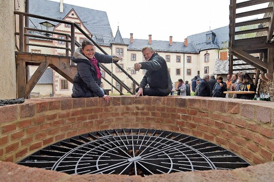 Burgchefin Susanne Tiesler und der technischer Leiter Jörg Nollau weihen den neuen, alten Burgbrunnen von Mildenstein mit einem Schluck Sekt ein.