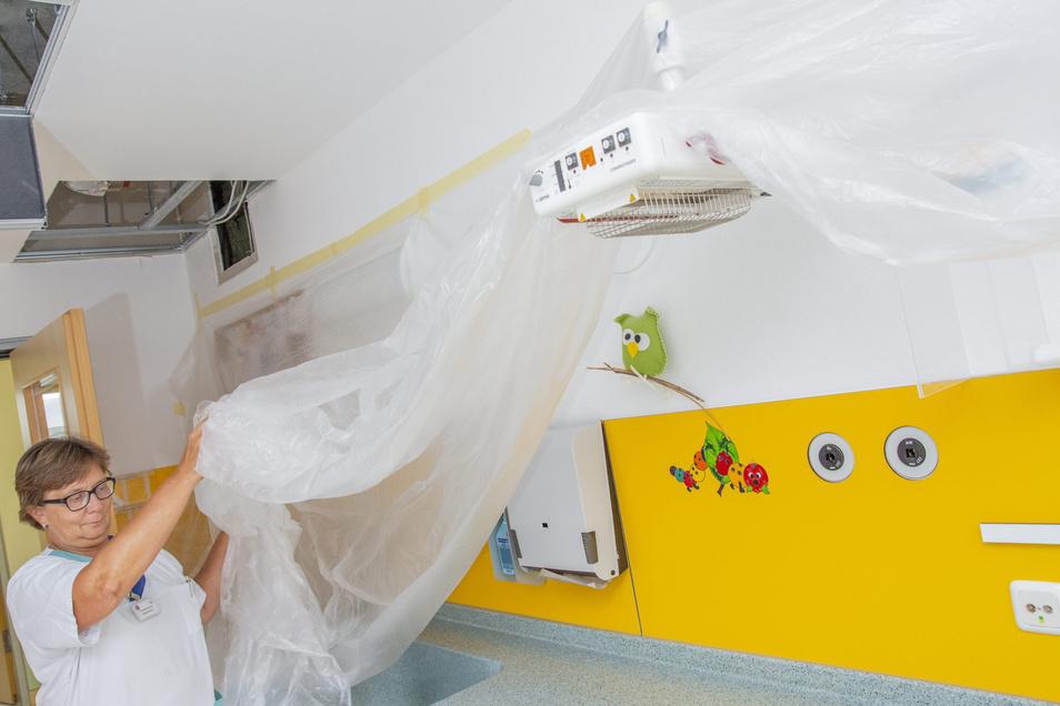 Kommen die Bauarbeiter, kann es staubig werden: Stationsschwester Bärbel zeigt, wie es im Stillzimmer des Riesaer Klinikums aussieht: Wickeltisch und Wärmelampe sind mit Folie abgedeckt, weil für eine neue Etage Leitungen in die Decke kommen.