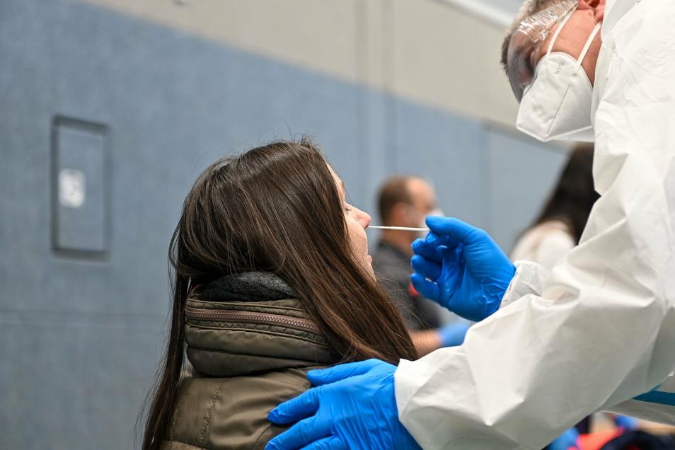 Eine junge Frau lässt sich in der Sporthalle von Räckelwitz auf das Coronavirus testen. Alle Einwohner der Gemeinde waren dazu am Freitag aufgerufen.