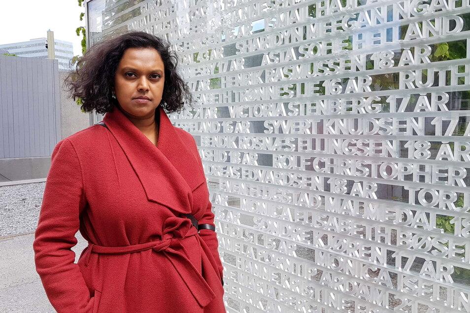 Kamzy Gunaratnam, stellvertretende Bürgermeisterin von Oslo, die den Anschlag auf Utøya überlebt hat, steht neben einem Denkmal im Regierungsviertel mit den Namen der 77 Todesopfer.