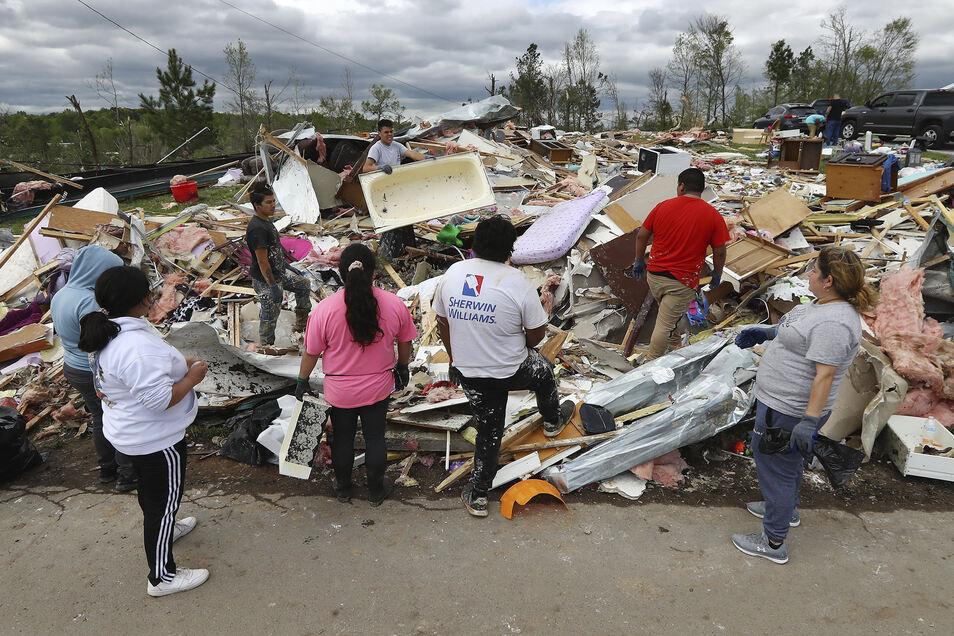 Eine Familie durchsucht die Trümmer ihres Wohnwagens.