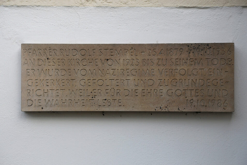 Die Sandsteintafel erinnert an Pfarrer Rudolf Stempel, der 50 Jahre vor dem Anbringen gestorben war. Angefertigt wurde sie vom Steinmetzmeister Karl-Heinz Rudolf. Rudolf Stempel war an der Kirche in Gröba von 1923 bis zu seinem Tode 1936 Pfarrer. Er war der erste sächsische Pfarrer, der von den Nazis in ein Konzentrationslager gebracht wurde.