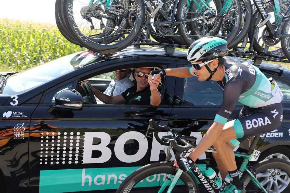 Enrico Poitschke gibt am Materialwagen seinem Fahrer Emanuel Buchmann Nahrungsnachschub und taktische Anweisungen. Die muss der Fahrer befolgen (, wenn er kann). Poitschke ist der Chef.