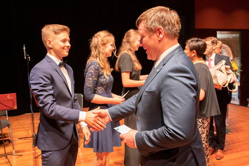 Paul Kümmel erhält Glückwünsche vom Großenhainer Oberbürgermeister Sven Mißbach. Auch Emma Würffel und Lydia Kedzierski gehören zu den besten Absolventen mit 1,0.