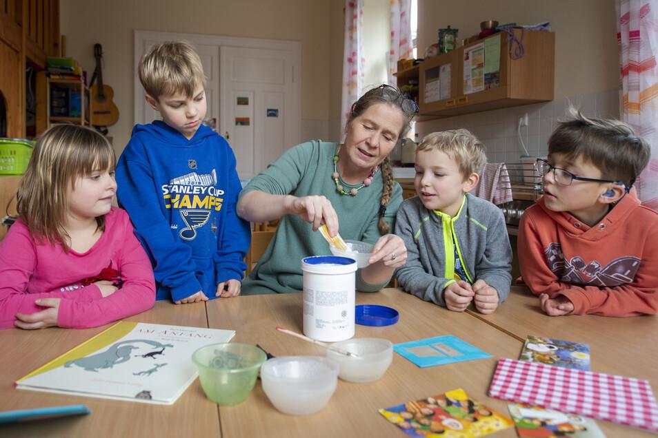 Literaturpädagogin Maike Beier bastelt mit den Kindern die Einbände.