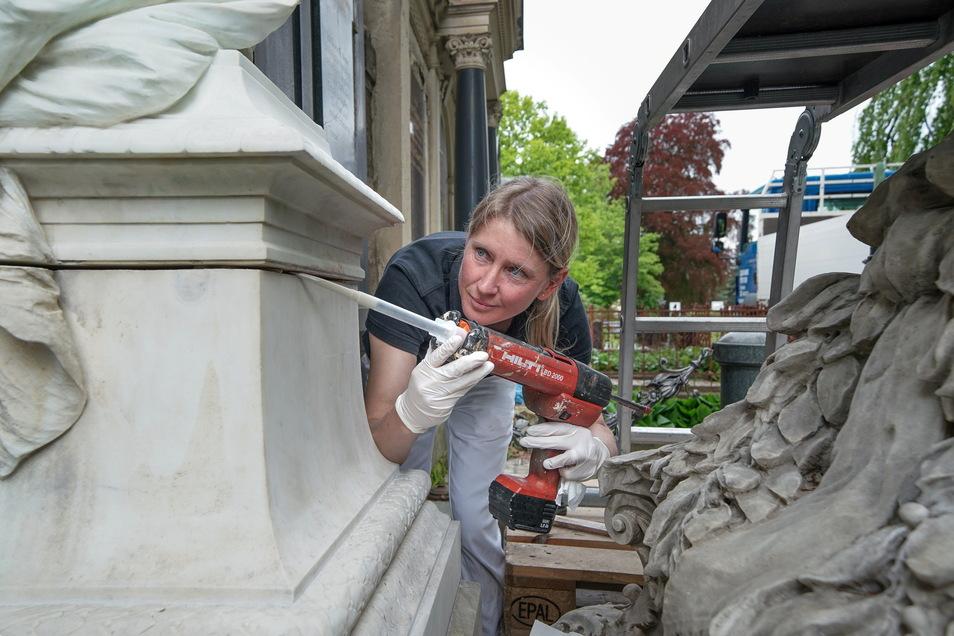Restauratorin Dana Krause verbindet mit Fugenmasse die Skulptur mit ihrem Sockel. Sie ist Expertin für historische Kunstwerke aus Marmor wie dieses.