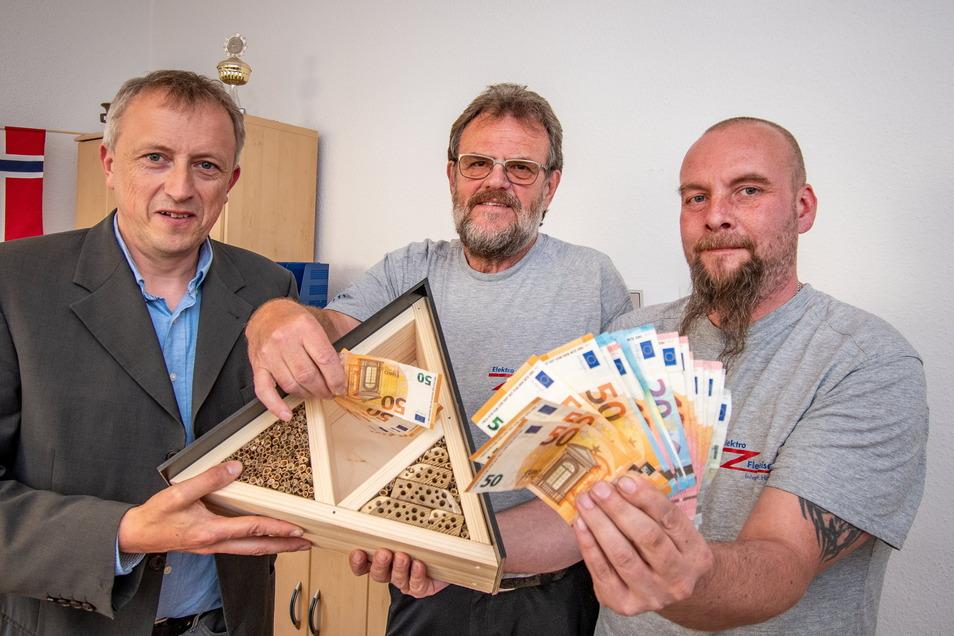 Der Inhaber von Elektro-Fleckeisen Markus Haupt (rechts) und Frank Fleckeisen übergeben dem Geschäftsführer der Diakonie Döbeln Thomas Richter die Spende in Höhe von 1.000 Euro.