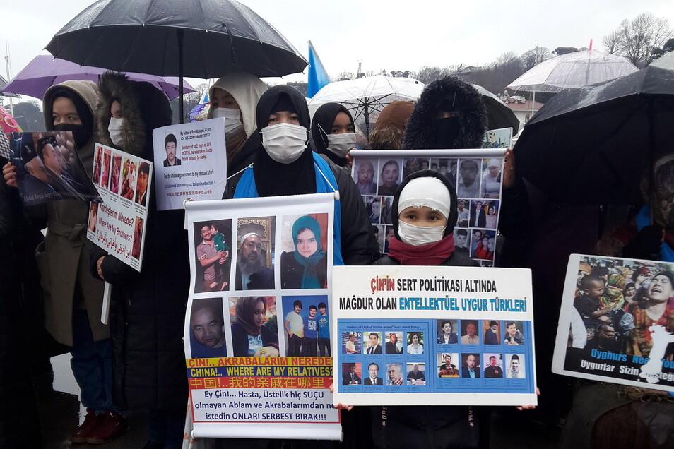 Mitglieder der uigurischen Gemeinschaft, die in der Türkei leben, halten in Istanbul Bilder von vermissten Familienmitgliedern hoch.