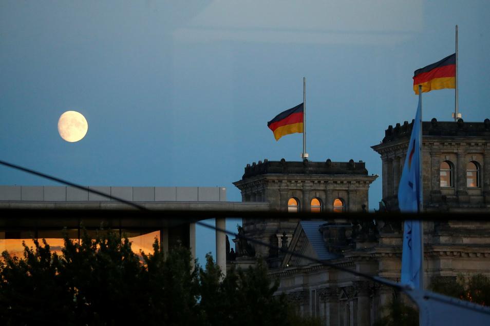 Der Mond ist am Himmel über dem Reichstagsgebäude in Berlin zu sehen, dem Sitz des Bundestages. Die neuen Corona-Maßnahmen von Bund und Ländern stoßen auf Kritik.