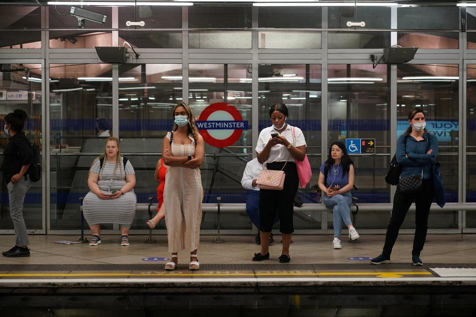 """Pendler stehen an der Westminster Station der Londoner U-Bahn: Immer häufiger macht es bei den Briten """"Ping"""" - trotz derzeit sinkender Infektionszahlen."""