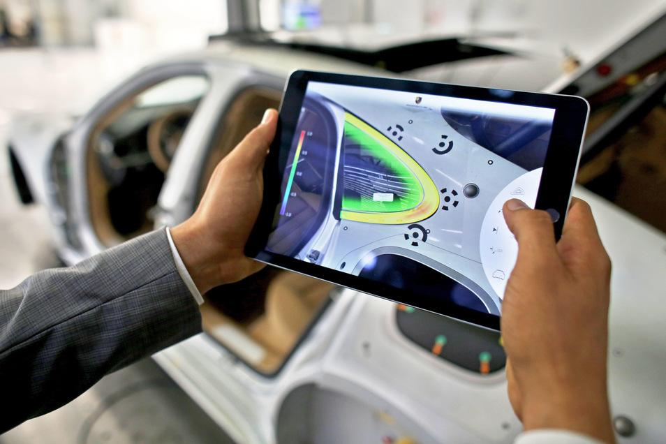 Ein Ingenieur bei Porsche in Leipzig scannt ein Seitenteil, um Abweichungen zu finden. Unter Koordination von Infineon Technologies arbeiten über 100 Partner aus 19 EU-Ländern an der Digitalisierung der Industrie. Porsche gehört dazu.