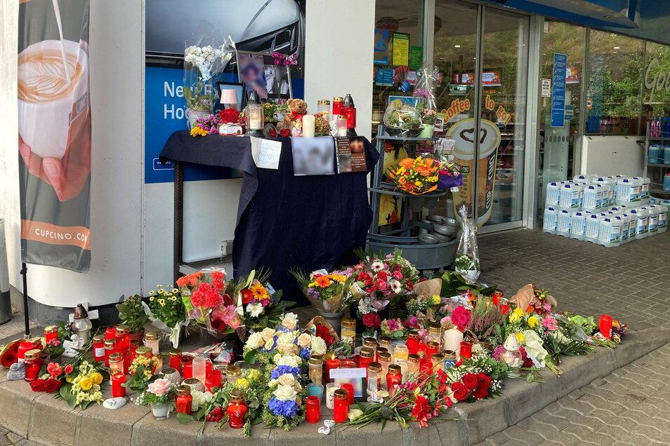 Blumen und Kerzen sind vor der Tankstelle in Idar-Oberstein aufgestellt.