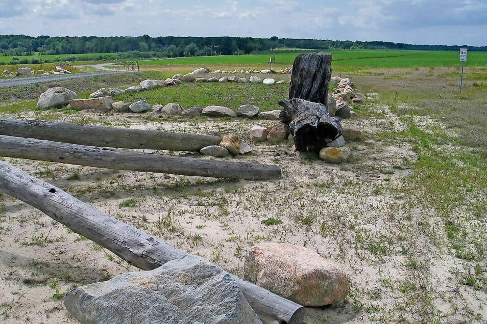 """Neben der Wanderhütte am Aussichtspunkt """"Altliebeler Höhe"""" deuten aus Steinen gebildete Rechtecke die Grundrisse der vier letzten Höfe des einstigen Altliebel an. Die 6.000 Jahre alten Mooreichen wurden bei der Umverlegung des Schöps' gefunden."""