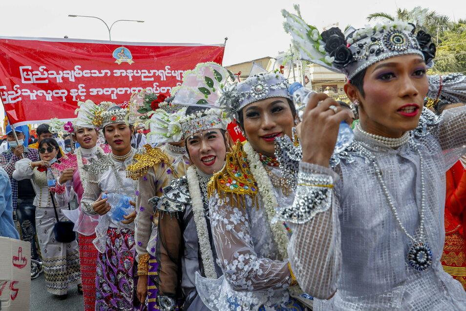 Demonstranten, geschminkt und gekleidet in traditionellen Tanzkostümen, marschieren gegen den Militärputsch.