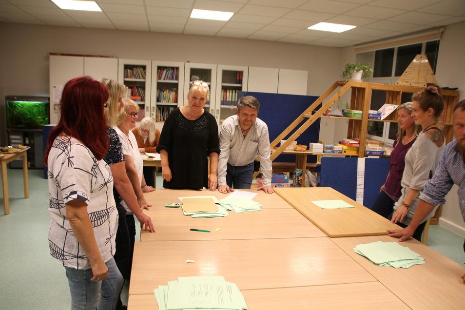 Leanne Streller, Lutz Grämer (Mitte) und die Wahlhelfer im Wahlbüro Glashütte 1 hatten am Sonntag viel zu tun. Das eingespielte Team hatte gegen 20 Uhr die beiden Wahlen ausgezählt.